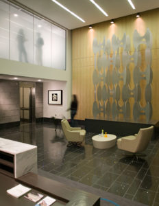 An interior lobby view of Plaza Midtown Apartments, with art and people on two floors
